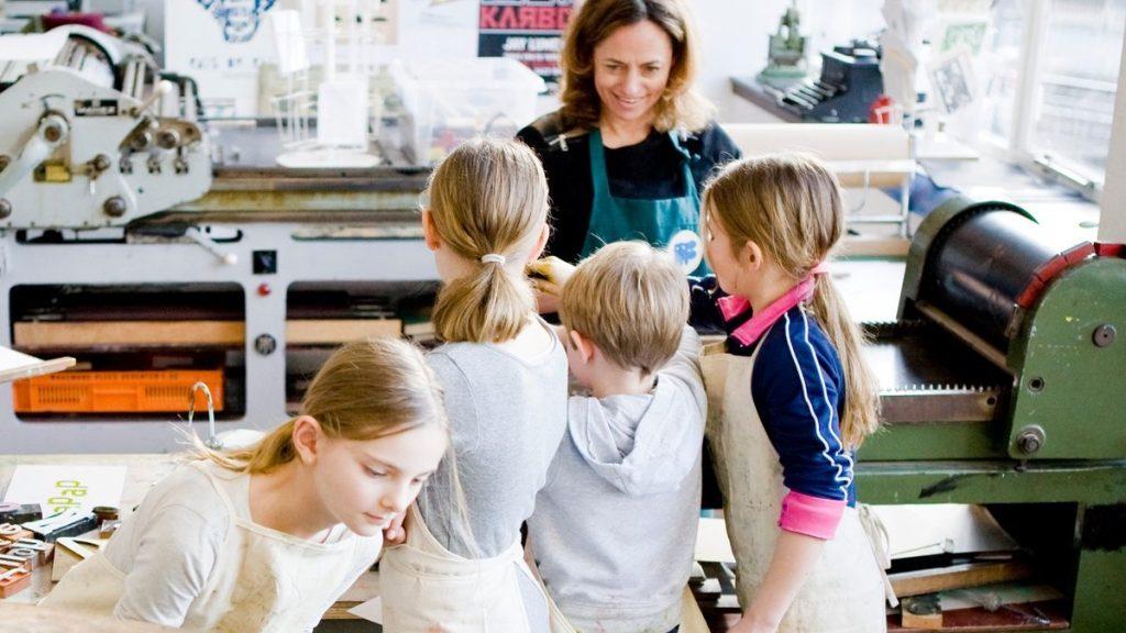 Een vrouw en vier kinderen met werkshorten werken aan een drukpers.